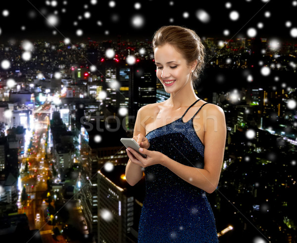 smiling woman in evening dress with smartphone Stock photo © dolgachov
