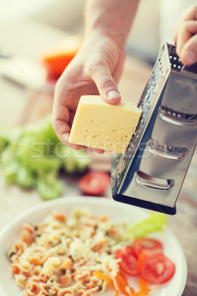 close up of male hands grating cheese over pasta Stock photo © dolgachov