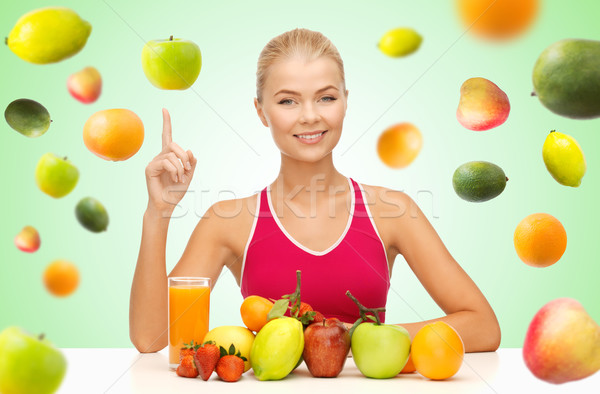 woman with juice and fruits pointing finger up Stock photo © dolgachov