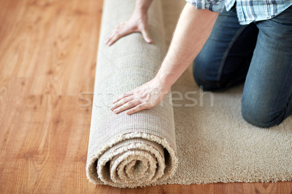 Stock photo: close up of male hands rolling carpet