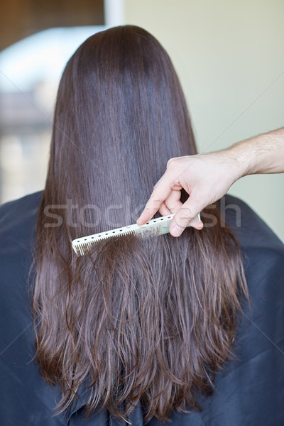 hand with comb combing woman hair at salon Stock photo © dolgachov