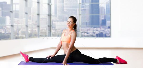 smiling woman doing splits on mat over gym Stock photo © dolgachov