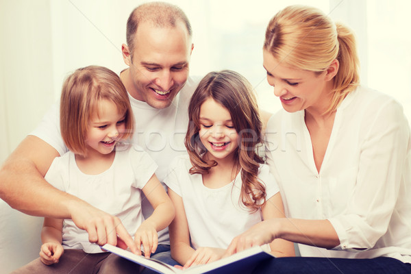 smiling family and two little girls with book Stock photo © dolgachov