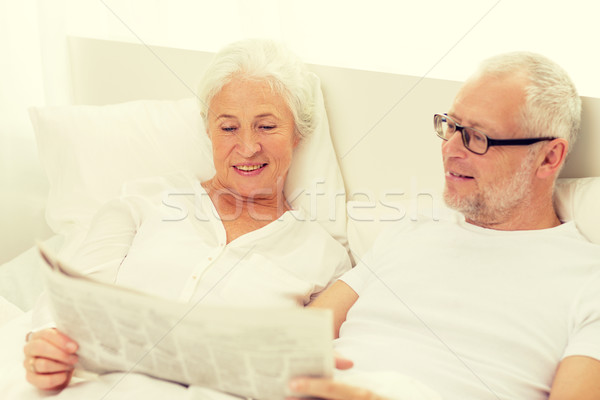Stock photo: happy senior couple with newspaper in bed