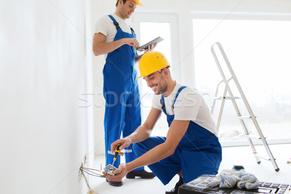 builders with tablet pc and fixing wiring indoors Stock photo © dolgachov