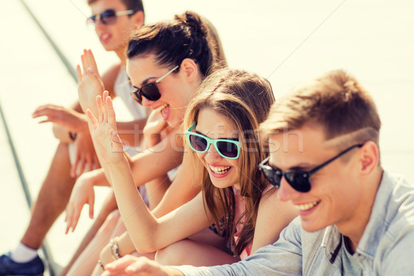 group of laughing friends sitting on city square Stock photo © dolgachov