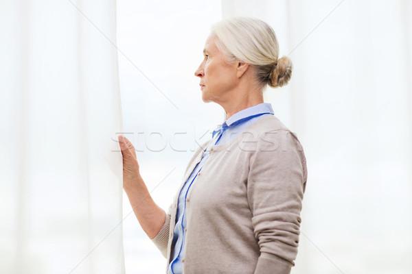 Yalnız kıdemli kadın bakıyor pencere ev Stok fotoğraf © dolgachov