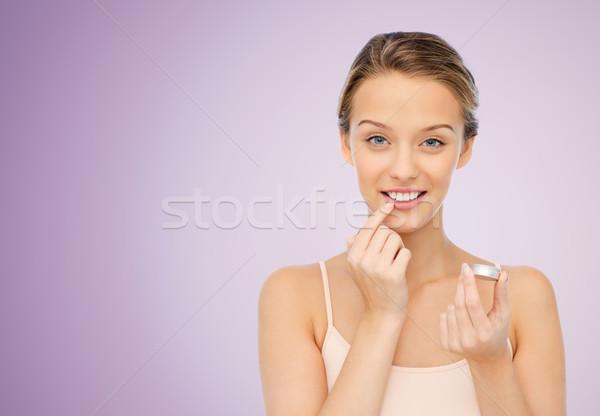 Mosolyog fiatal nő jelentkezik ajak balzsam ajkak Stock fotó © dolgachov