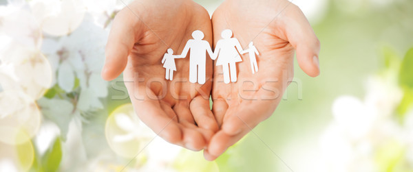 man hands holding paper cutout of family Stock photo © dolgachov