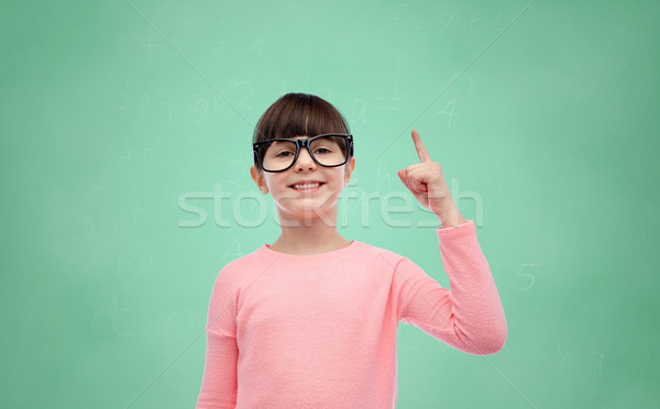 happy little girl in eyeglasses pointing finger up Stock photo © dolgachov