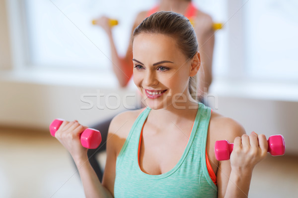 Stock photo: smiling woman with dumbbells exercising in gym