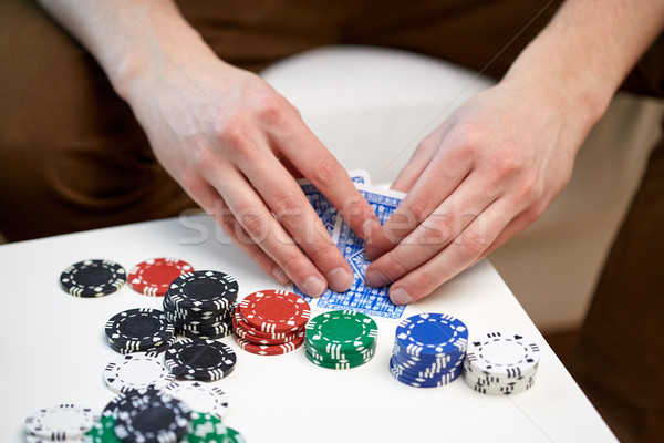 close up of male hand with playing cards and chips Stock photo © dolgachov