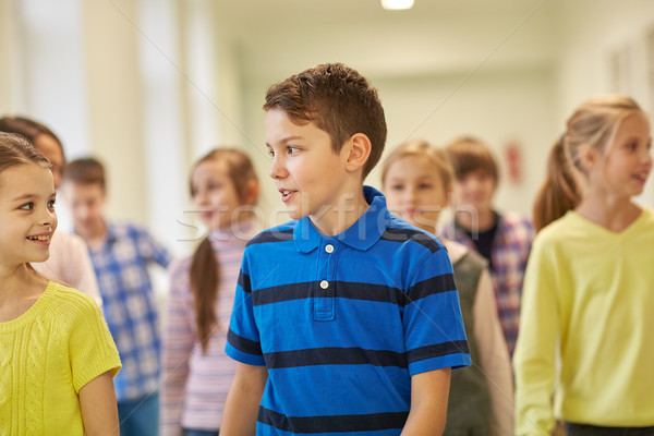 group of smiling school kids walking in corridor Stock photo © dolgachov