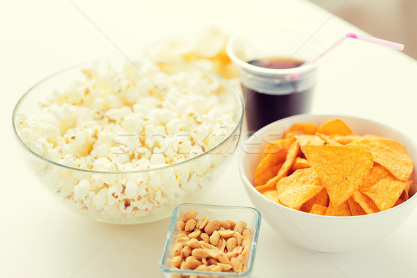 Stock photo: close up of popcorn and corn crisps or nachos