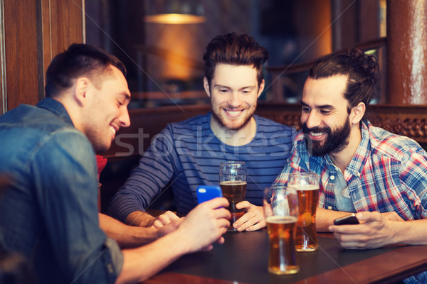 male friends with smartphones drinking beer at bar Stock photo © dolgachov