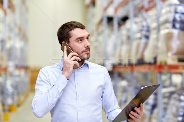 man with clipboard and smartphone at warehouse Stock photo © dolgachov