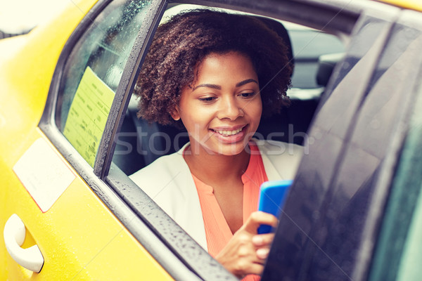 happy african woman texing on smartphone in taxi Stock photo © dolgachov