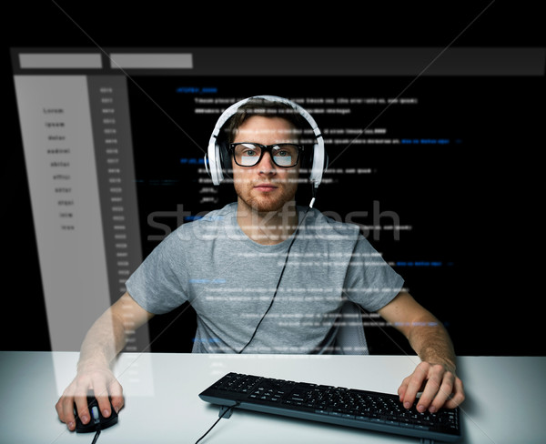 man in headset hacking computer or programming Stock photo © dolgachov