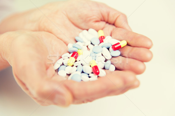 close up of senior woman hands with pills Stock photo © dolgachov