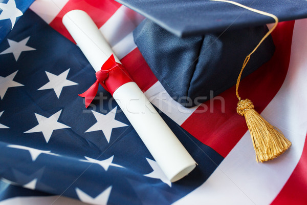 mortarboard and diploma on american flag Stock photo © dolgachov