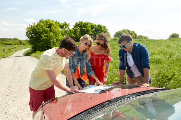happy friends with map and car at country road Stock photo © dolgachov