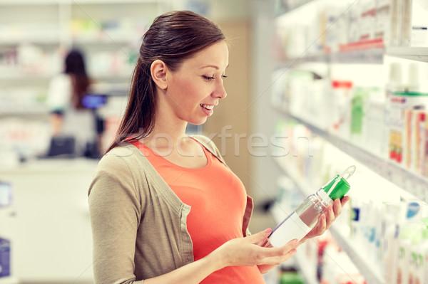 Feliz mulher grávida escolher loção farmácia gravidez Foto stock © dolgachov