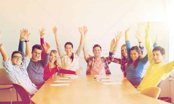 group of smiling students raising hands in office Stock photo © dolgachov