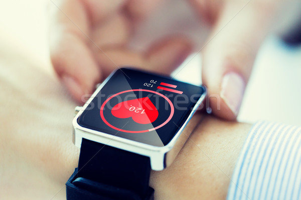 close up of hands with heart icon on smartwatch Stock photo © dolgachov