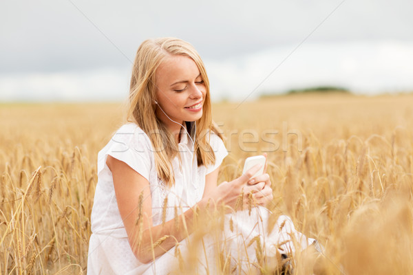 Stock photo: happy woman with smartphone and earphones