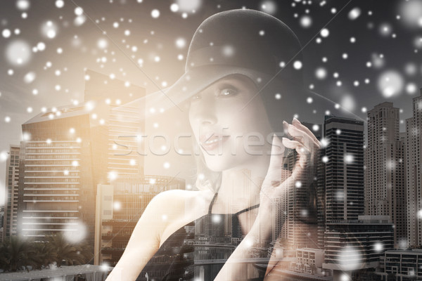 woman in black hat over city background and snow Stock photo © dolgachov