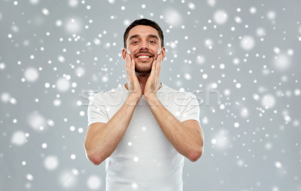 happy man applying aftershave or cream to face Stock photo © dolgachov