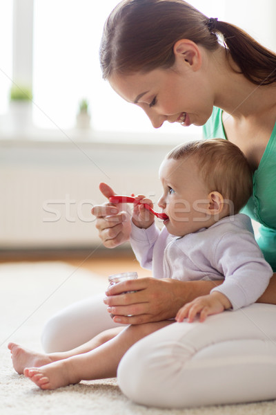 happy mother with spoon feeding baby at home Stock photo © dolgachov