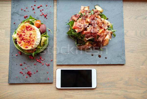goat cheese and ham salads with smartphone at cafe Stock photo © dolgachov