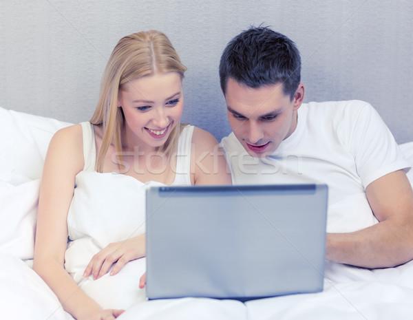 Glimlachend paar bed laptop computer hotel reizen Stockfoto © dolgachov