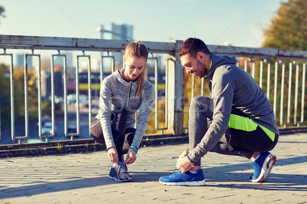 Stock photo: smiling couple tying shoelaces outdoors