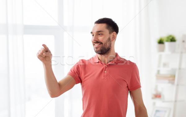 Heureux homme toucher quelque chose imaginaire maison Photo stock © dolgachov