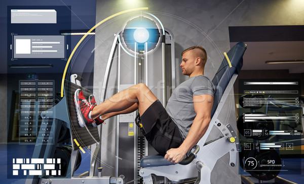 man flexing leg muscles on gym machine Stock photo © dolgachov