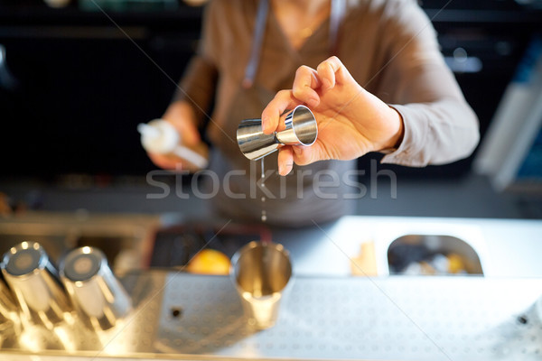 bartender with cocktail shaker and jigger at bar Stock photo © dolgachov