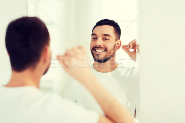 man cleaning ear with cotton swab at bathroom Stock photo © dolgachov