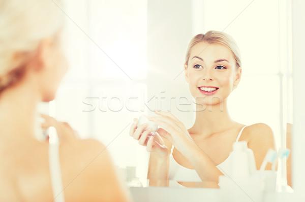 happy woman applying cream to face at bathroom Stock photo © dolgachov