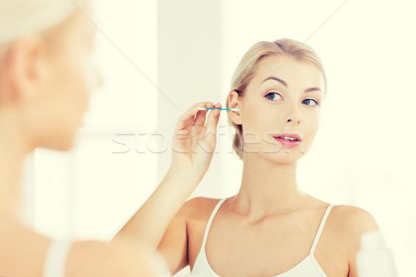 woman cleaning ear with cotton swab at bathroom Stock photo © dolgachov