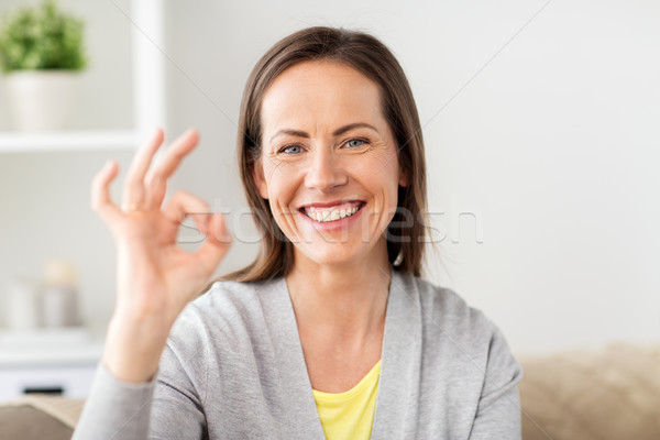 happy smiling woman showing ok hand sign at home Stock photo © dolgachov