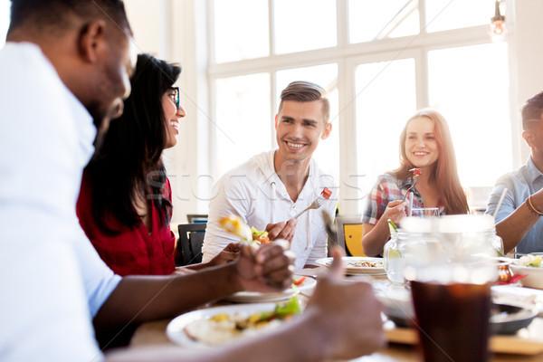 Felice amici mangiare parlando ristorante tempo libero Foto d'archivio © dolgachov
