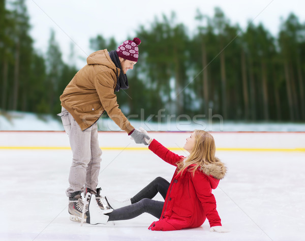 man helping woman to rise up on skating rink Stock photo © dolgachov