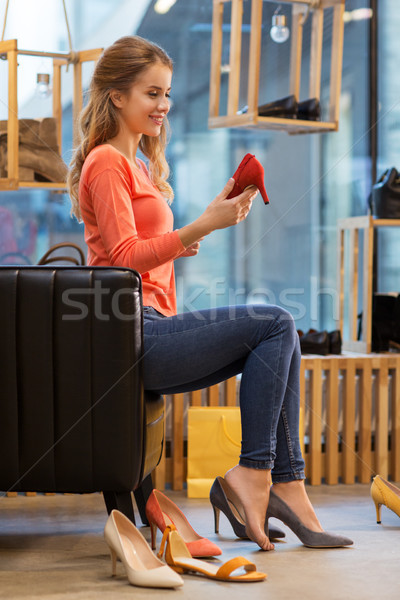 young woman trying high heeled shoes at store Stock photo © dolgachov