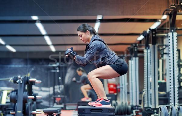 woman doing squats on platform in gym Stock photo © dolgachov