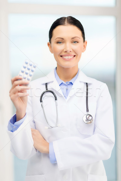 smiling young doctor with pills and sthethoscope Stock photo © dolgachov
