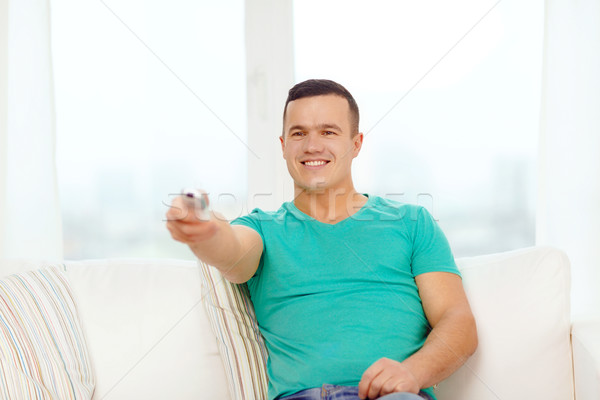 smiling man with tv remote control at home Stock photo © dolgachov