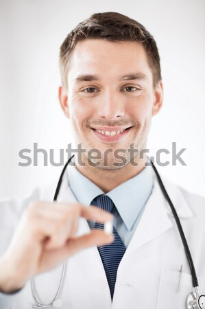young male doctor offering pill Stock photo © dolgachov