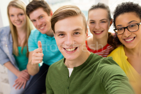 five smiling students taking selfie at school Stock photo © dolgachov